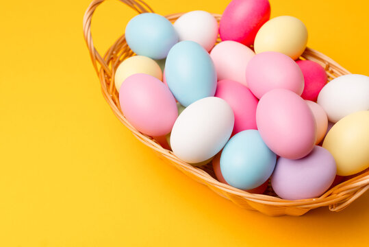 Photo of colorful easter eggs in basket over yellow background