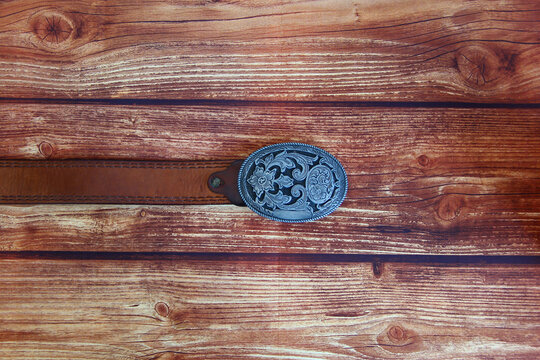 Leather cowboy belt with oval patterned buckle on a wooden background