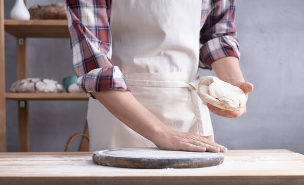 Baker man kneading or making dough and bakery ingredients for homemade bread cooking on shelf