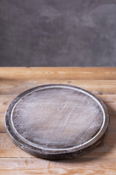 Pizza or bread cutting board and scattered wheat flour powder for homemade baking on wooden table