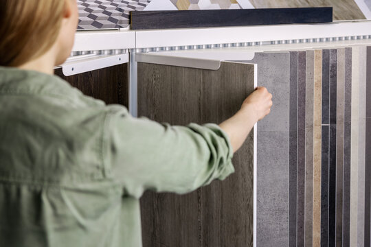 woman looking at laminate material samples in interior design shop