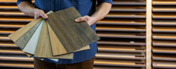 Obraz flooring store seller with vinyl floor samples in hands. copy space - fototapety do salonu
