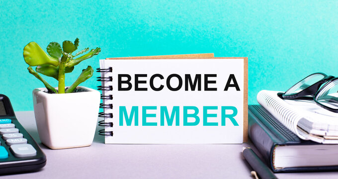 BECOME A MEMBER is written on a white card next to a potted flower, diaries and calculator. Organizational concept