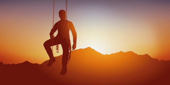 Concept de sport extrême, avec un alpiniste suspendu à une parois par des corde devant un coucher de soleil sur une chaine de montagne.