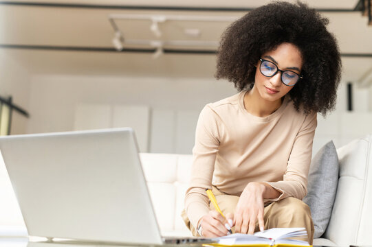 Smart young African American student or businesswoman sitting on the couch with laptop, studying from home, watching online webinar, taking notes to the notebook, making to do list, planning her week