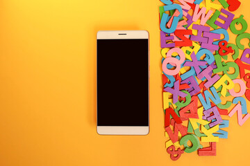 Smartphone and pile of colorful block letters on the yellow background