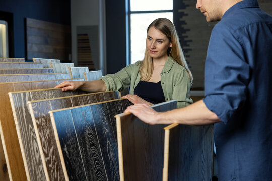 young couple choosing wood texture laminate floor from samples in flooring store for house improvements