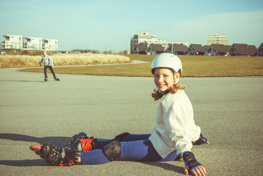 Portrait of pretty little teenager child girl sitting in white helmet, inline skates and safety equipment