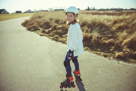 Happy child girl in white helmet, inline skates and safety equipment having fun during skating at sunny day