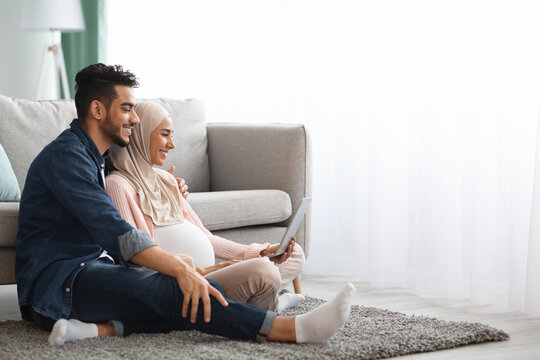 Happy pregnant muslim woman and her husband using laptop together at home