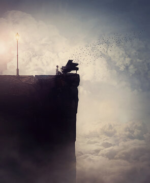 Person silhouette on the edge of a cliff sings and plays a piano song, as flock of birds flying out of the musical instrument. Surreal and inspirational scene above clouds. Adventure and music concept