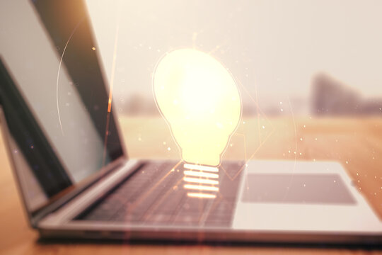 Double exposure of creative light bulb hologram on laptop background, research and development concept