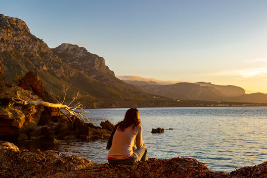 A young and beautiful girl dressed in casual clothes looking at the sunset at a beautiful beach in Artà Mallorca Balearic Islands Spain with a impressive view of the sea and the Tramuntana mountains
