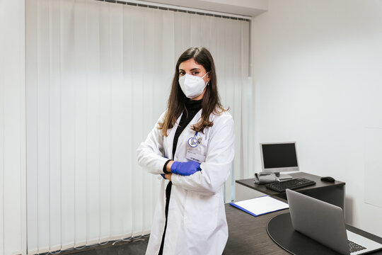 Portrait of young female doctor in medical office at hospital with arms folded wearing protective mask during Coronavirus Covid-19 infection pandemic - Concept of professionalism - Copy space