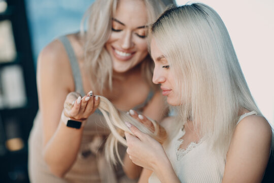 Hairdresser female making hair extensions to young woman with blonde hair in beauty salon. Professional strand hair extension.