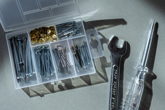 Transparent nail organizer box. Nails of different sizes. Key and screwdriver. Male repair tool kit.