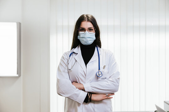 Portrait of young female doctor in medical office at hospital with arms folded wearing protective surgical mask during Coronavirus Covid-19 infection pandemic - Concept of professionalism - Copy space