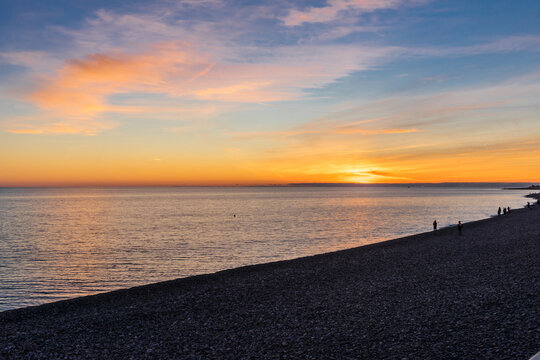 Pebble beach and beautiful sunset in Sochi, in Adler in spring. Silhouettes of people on the beach