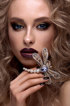Beautiful blonde girl with curls, bright make-up and designer accessories. Beauty face.