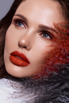 Beautiful woman with classic holiday make-up, red lips, curls in a multi-colored llama coat. Beauty face.