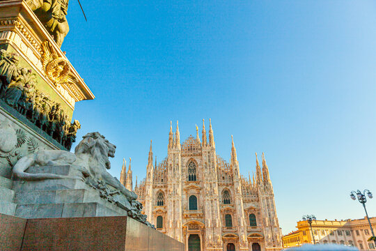 Lion marble statue near famous church Milan Cathedral Duomo di Milano. Panoramic view of top tourist attraction on piazza in Milan Lombardia Italy. Wide angle view of old Gothic architecture and art