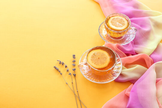 Two teacups with lemon slices, lavender branches on a yellow background, space for text