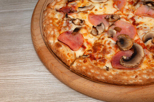 Pizza with ham, mushrooms and cheese on a board