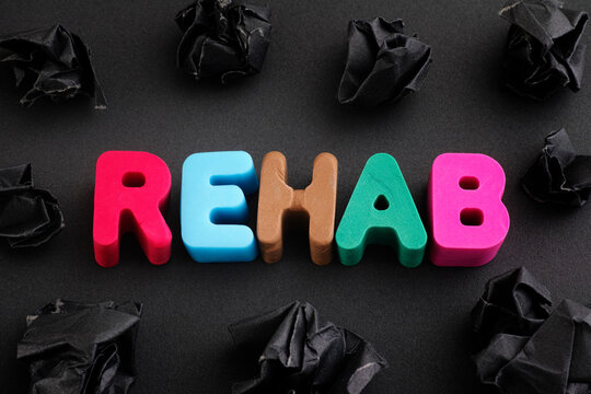 The word Rehab made out of polymer clay letters with some black crumpled paper balls around it