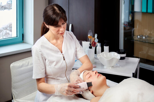 A cosmetologist in a medical gown does a facial cleansing procedure for a client. Beauty salon. Professional skin care products.