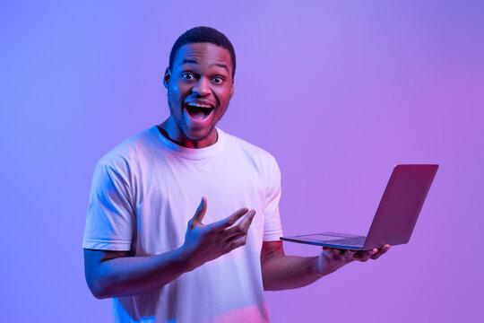 Cool Website. Excited Black Man With Laptop In Hands Under Neon Lighting