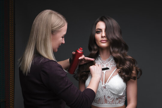 Hairdresser and beautiful brunette girl with a perfectly curls hair and classic make-up. Beauty face.