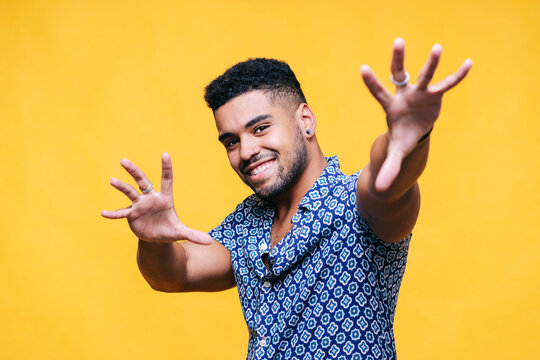 Smiling man gesturing against yellow background