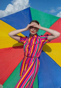 Beautiful woman shielding eyes against colorful beach umbrella
