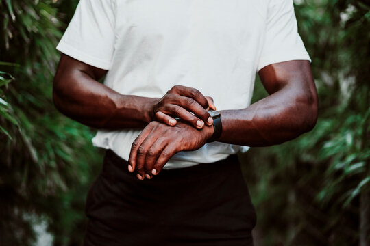 Sportsman checking smart watch while standing outdoors