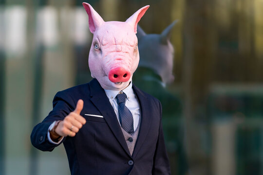 Young businessman wearing pig mask doing thumbs up against office building