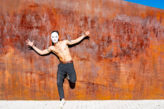 Shirtless man wearing white mask dancing with arms outstretched while standing against brown wall