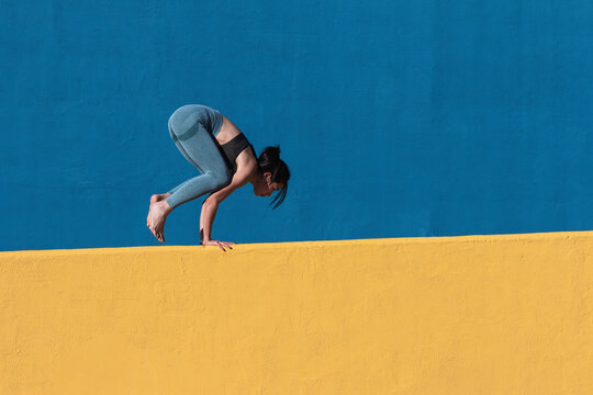 Strong woman doing handstand by wall