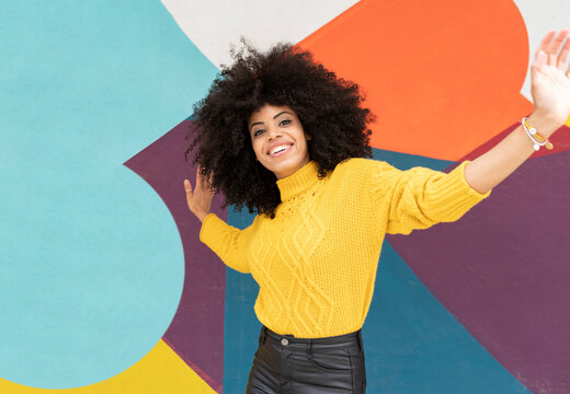 Young woman with arms outstretched smiling while dancing against colorful wall