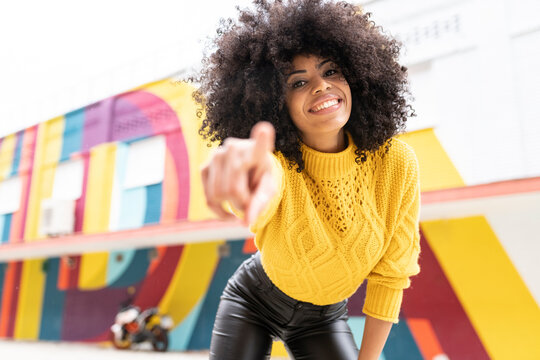 Smiling woman pointing finger while standing outdoors