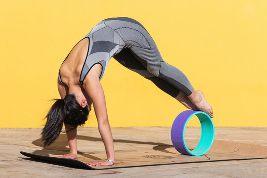 Woman doing Kumbhakasana with yoga wheel by yellow wall