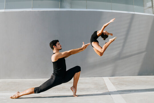 Female gymnast doing acrobat while male dancer practicing stag leap by gray wall