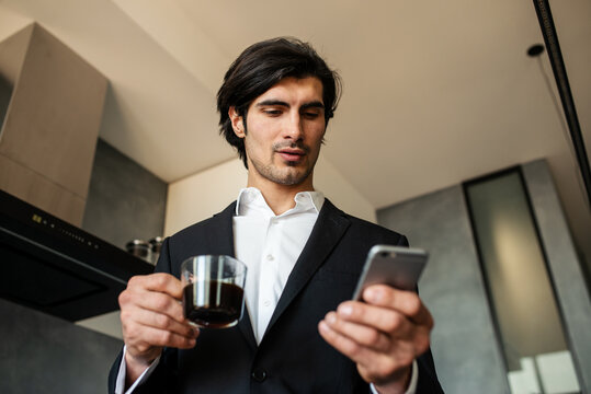 Businessman read news from smartphone while drinking a coffee at home