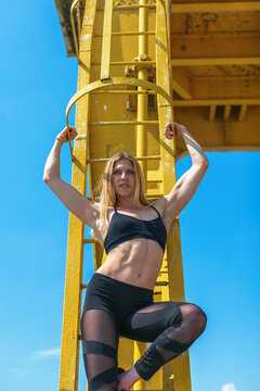 muscular nd fit young woman standing on an old metal crane
