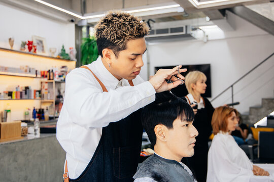 Asian male customer getting hair cut with hairdresser in salon. Fashionable barber using a scissor to trim client hair in barbershop