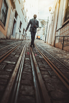 A dapper bald bearded guy in an elegant custom-made business costume and eyeglasses is leaning on his walking stick while staying in the middle of a narrow antique European street on the tramway track
