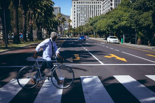 African american senior man wheeling bicycle across road on a pedestrian crossing