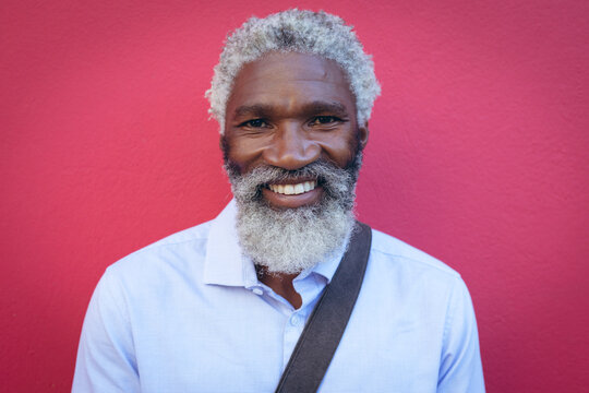 Portrait of african american senior man with beard standing against red wall in the street smiling