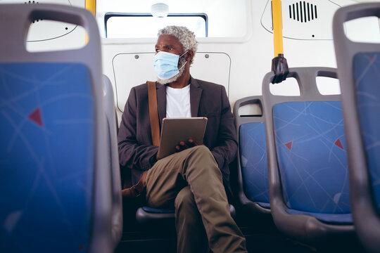 African american senior man wearing face mask sitting on bus using digital tablet