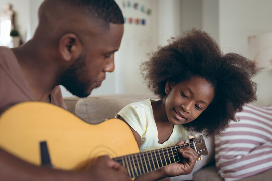 African american man and his daughter sitting on couch man is playing guitar