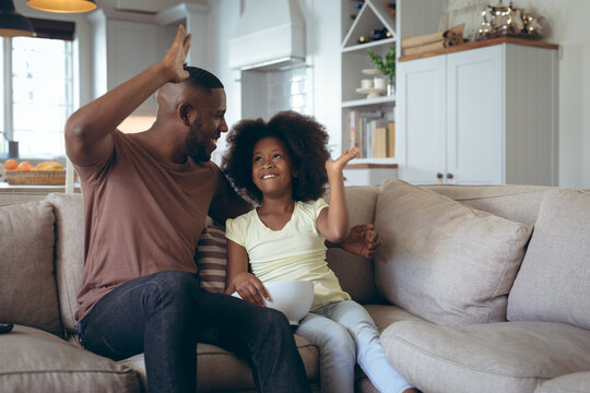 African american man and his daughter sitting on couch high fiving